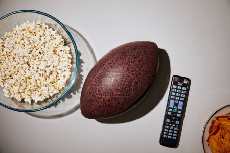 Photo for Top view of delicious snacks in glass bowls near football and remote control on white background - Royalty Free Image