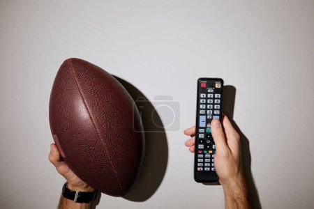 Photo for Cropped view of man holding remote control and brown ball on white background - Royalty Free Image