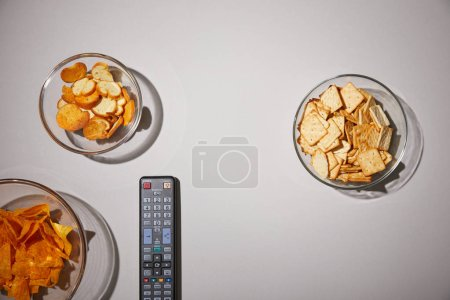 Photo for Top view of glass bowls with tasty snacks near remote control on white background - Royalty Free Image