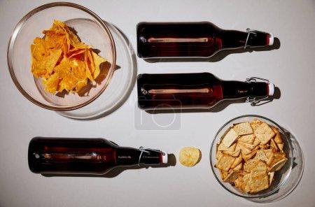 vue du dessus des bouteilles avec de la bière près de collations savoureuses sur fond blanc