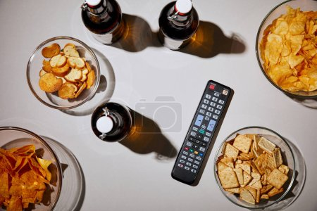 Photo for Top view of bottles with beer near remote control and snacks in bowls on white background - Royalty Free Image