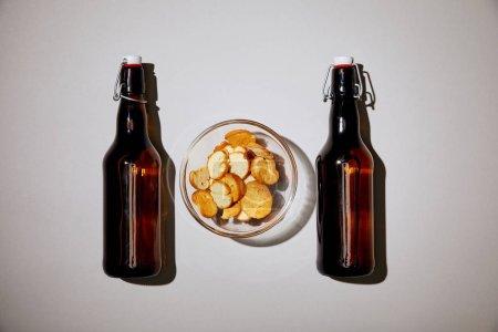 vue du dessus des bouteilles brunes avec bière près de collation dans un bol sur fond blanc