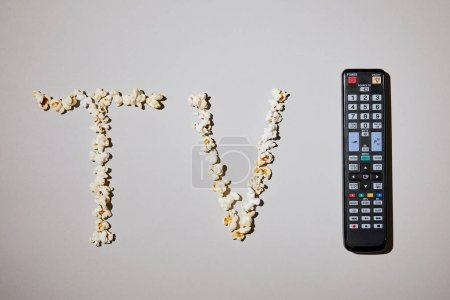 Photo for Top view of tasty popcorn with tv lettering with remote control on white background - Royalty Free Image