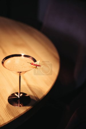alcoholic cocktail in metal glass decorated with chili pepper and nacho chip on wooden table