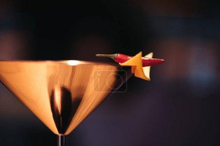 Foto de Cerca del cóctel alcohólico en vidrio decorado con chile pimiento y nacho chip sobre fondo oscuro - Imagen libre de derechos