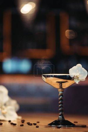 Photo pour Cocktails alcoolisés en métal verre orné de fleur d'orchidée sur fond sombre avec espace copie - image libre de droit