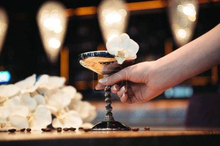 Photo pour Vue recadrée de femme tenant des cocktails alcoolisés en métal verre orné de fleur d'orchidée - image libre de droit