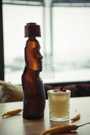 Foto de Estatua de bronce y alcohólica cóctel adornado con naranja seca y pimientos en mesa en el restaurante - Imagen libre de derechos