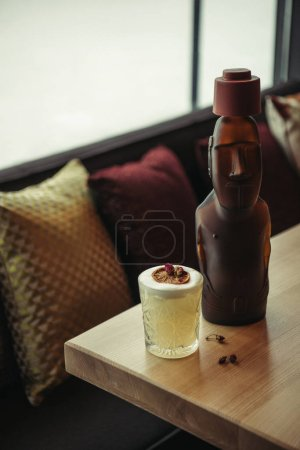 Photo for Bronze statue and alcoholic cocktail decorated with dry orange on wooden table in restaurant - Royalty Free Image