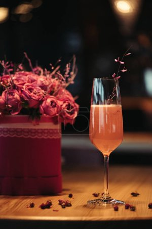 Photo for Selective focus of pink alcoholic cocktail with flowers on dark background - Royalty Free Image