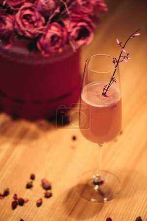 Photo for Selective focus of pink alcoholic cocktail decorated with dry flowers on wooden background - Royalty Free Image