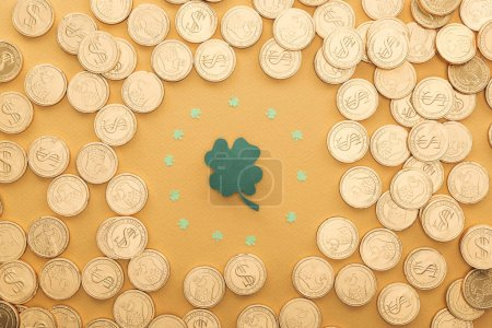 Photo for Top view of golden coins with dollar signs and circle of shamrocks isolated on orange, st patrick day concept - Royalty Free Image