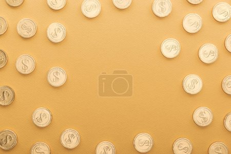 Photo for Top view of shiny golden coins with dollar signs isolated on orange with copy space, st patrick day concept - Royalty Free Image