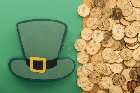 Photo for Top view of golden coins with dollar signs and paper hat on green and orange background, st patrick day concept - Royalty Free Image