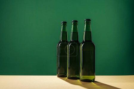 Photo pour Bouteilles de bière avec les ombres et espace copie isolée sur vert, st concept jour patrick - image libre de droit