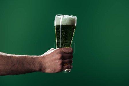 Photo pour Vue partielle de l'homme portant des verres de bière avec la mousse isolé sur vert, st concept jour patrick - image libre de droit