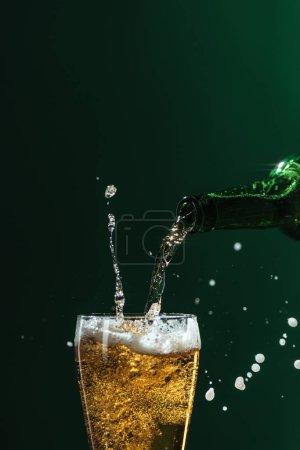 Photo pour Verser la bière dans verre avec éclaboussures et espace copie isolée sur vert, st concept jour patrick - image libre de droit