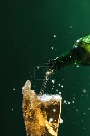 Photo for Pouring beer into glass with splashes and copy space isolated on green, st patrick day concept - Royalty Free Image