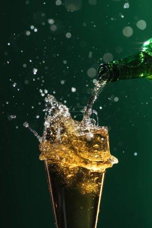 Photo pour Verser la bière dans verre avec éclaboussures isolés sur vert, st concept jour patrick - image libre de droit