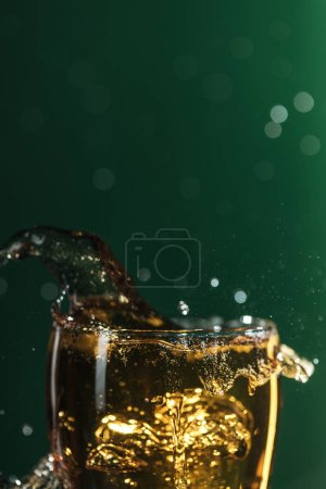Photo for Glass of beer with splashes isolated on green with copy space, isolated on green - Royalty Free Image