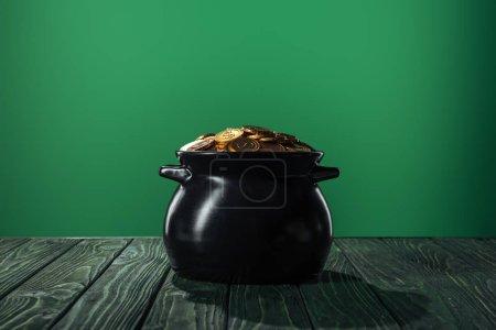 Photo pour Pièces d'or en pot noir isolé sur vert, concept st patrick jour - image libre de droit