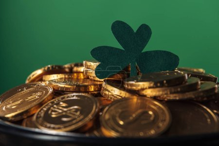 Photo for Shiny golden coins with shamrock isolated on green, st patrick day concept - Royalty Free Image