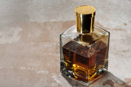 Photo for Close-up view of bottle of amber bourbon on grey grunge surface - Royalty Free Image
