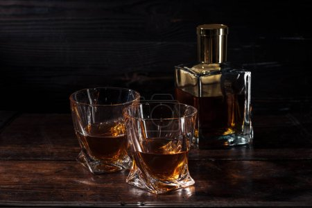 Photo for Bottle and glasses of whisky on brown wooden table - Royalty Free Image