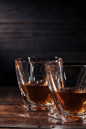 Photo for Close-up view of two glasses of whisky on dark wooden table - Royalty Free Image