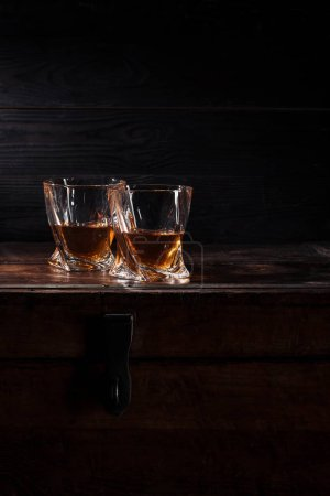 Photo for Two glasses of whiskey on vintage wooden table - Royalty Free Image