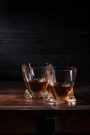 Photo for Two glasses of whiskey on brown wooden table - Royalty Free Image