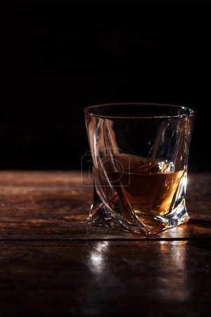 Photo for Close-up view of brandy in glass on wooden table on black - Royalty Free Image