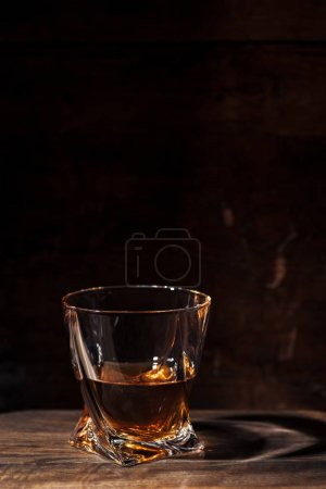 Photo for Close-up view of whiskey in glass and reflection on wooden table - Royalty Free Image