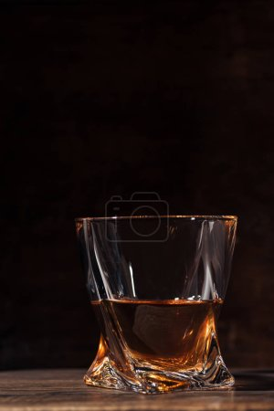 Photo for Close-up view of whiskey in glass on wooden table on black - Royalty Free Image