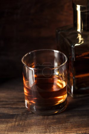 Photo for Close-up view of glass of bourbon and bottle on wooden table - Royalty Free Image