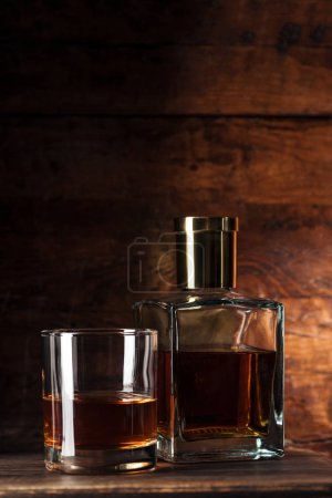 Photo for Close-up view of glass of brandy and bottle on wooden table - Royalty Free Image