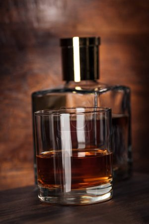 Photo for Close-up view of glass of cognac and bottle on wooden table - Royalty Free Image