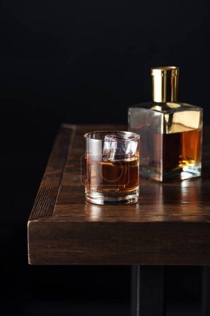Photo for Close-up view of glass and bottle of whisky on dark wooden table isolated on black - Royalty Free Image