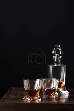 Photo for Glasses and bottle of whisky on dark wooden table isolated on black - Royalty Free Image