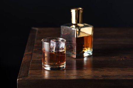 Photo for Glass and bottle of whisky on dark wooden table isolated on black - Royalty Free Image