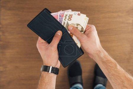 Photo pour Vue de dessus de l'homme mettant UAH billets en portefeuille sur fond en bois - image libre de droit