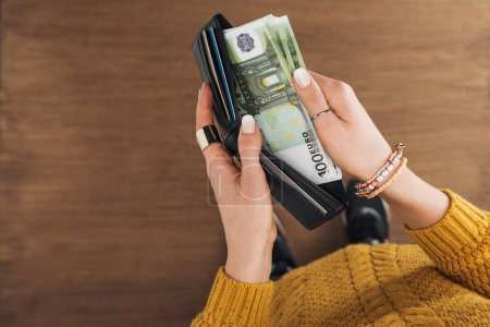 top view of woman taking from wallet euros banknotes on wooden background