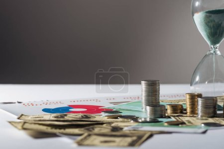 Photo for Selective focus of coins stacks, hourglass on dollar and euro banknotes - Royalty Free Image