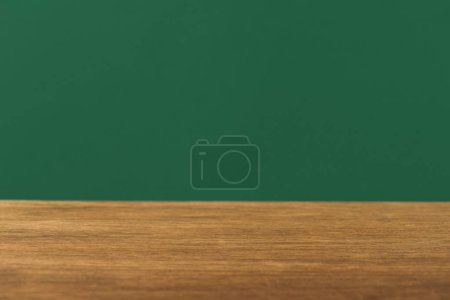 empty wooden table on green background with copy space