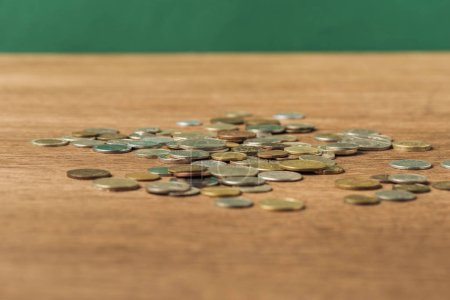Photo for Selective focus of coins on wooden table and green background - Royalty Free Image