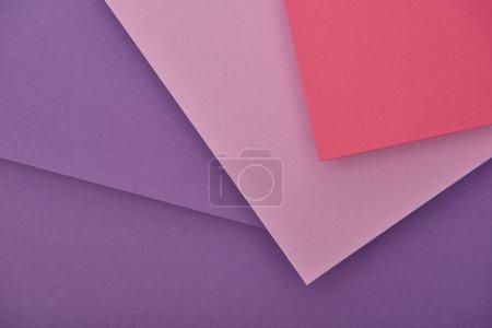 Draufsicht auf fliederfarbene, violette und rosa Papierblätter mit Kopierraum