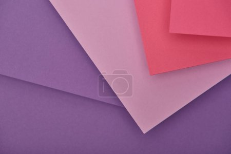 top view of purple and pink paper sheets with copy space