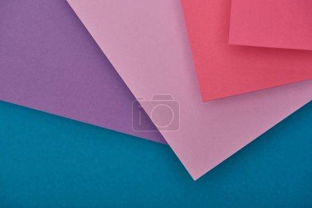 Photo pour Vue de dessus des feuilles de papier violet, bleu et fuchsia avec espace copie - image libre de droit