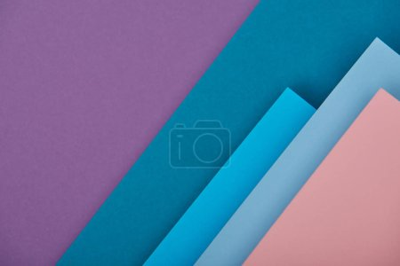 top view of purple, blue and pink paper sheets with copy space