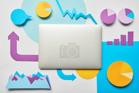 top view of laptop, charts and graphs, pointers made of paper on white background